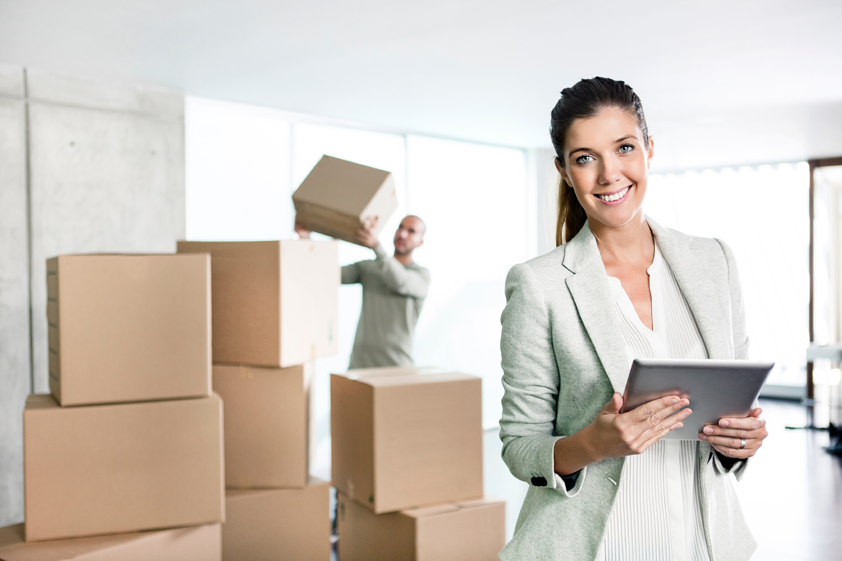 smiling woman in front of man stacking boxes