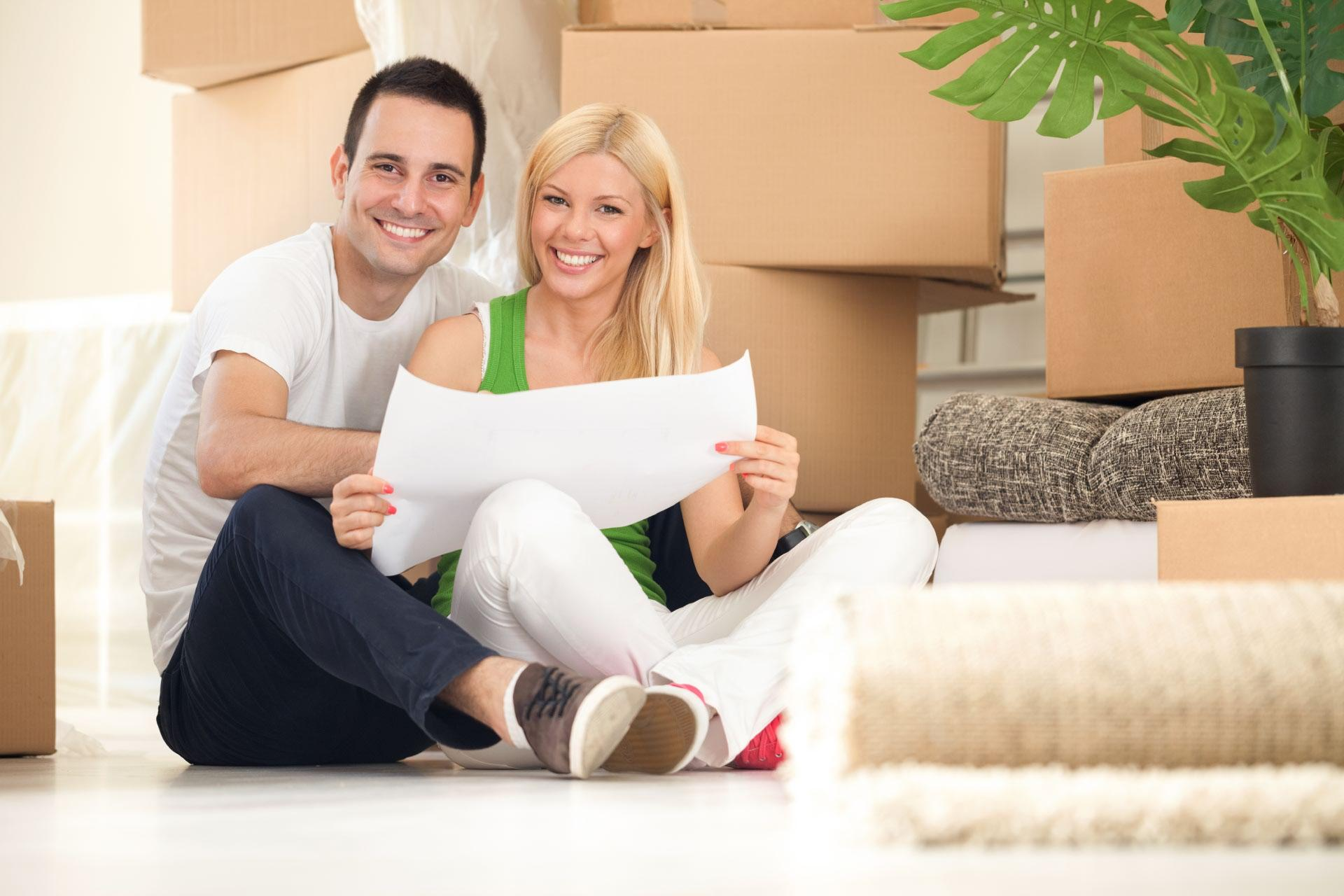 Happy young couple sitting in front of boxes