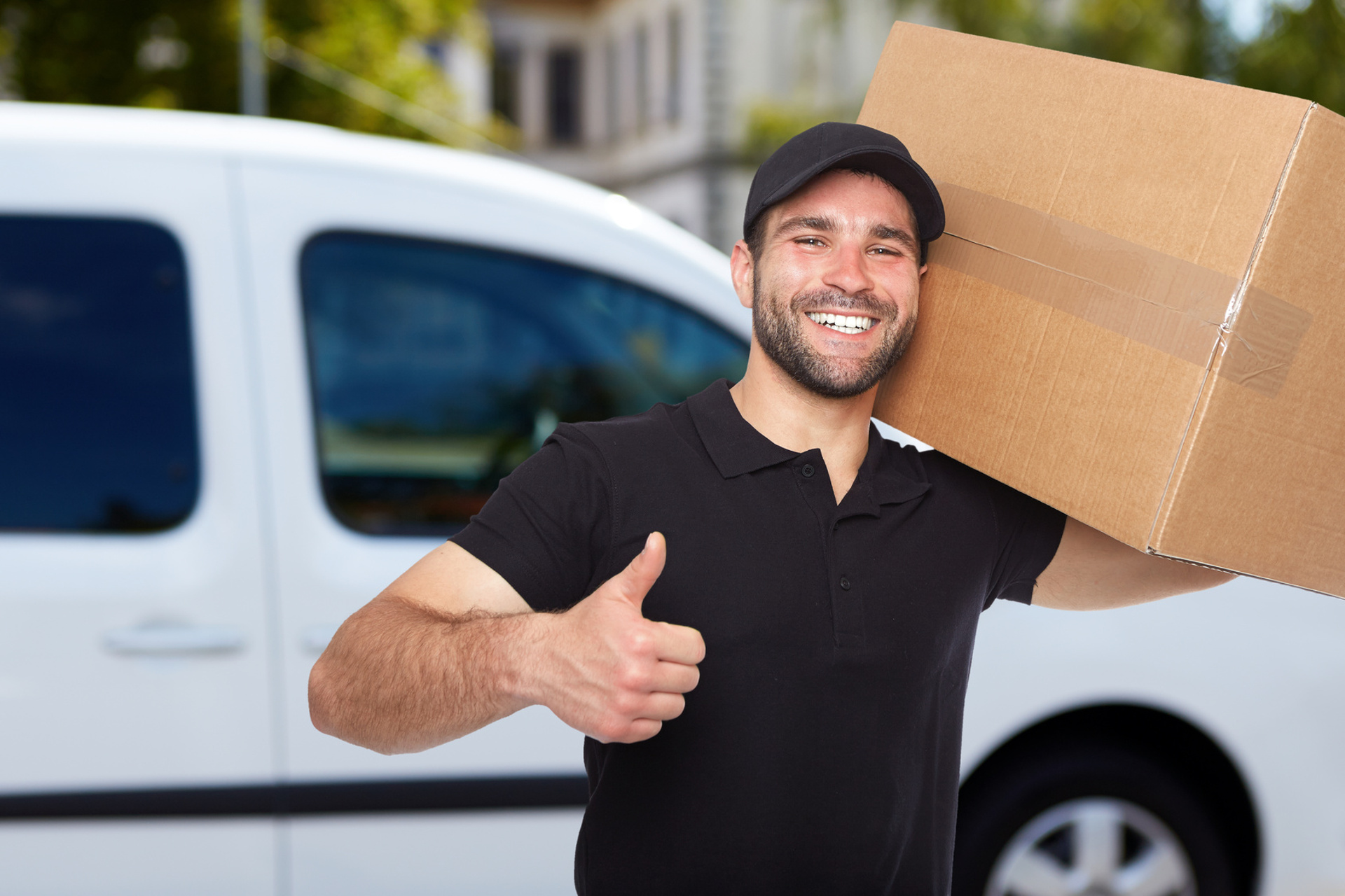 smiling man carrying a moving box on shoulder