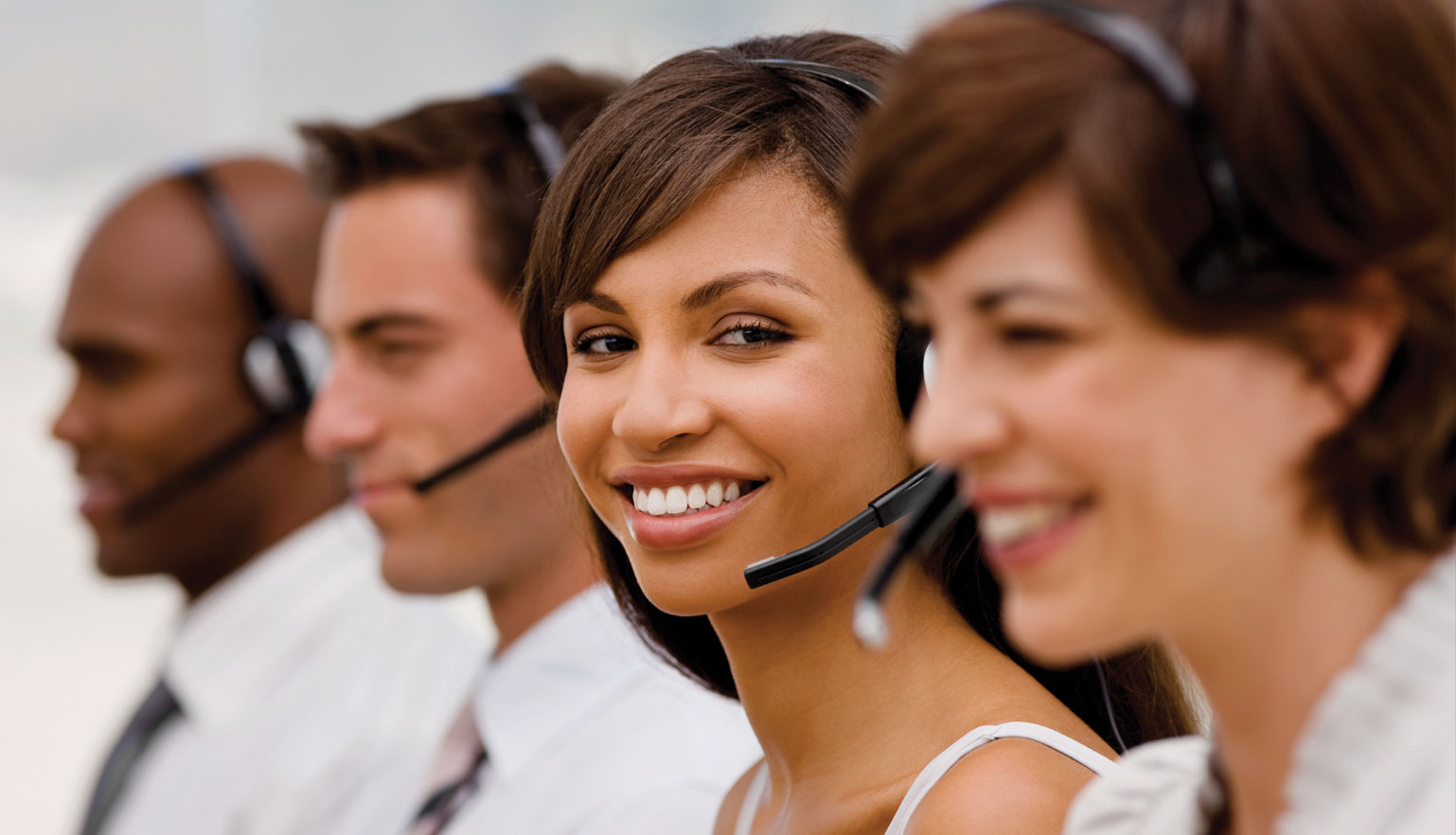 4 smiling customer services reps on headsets