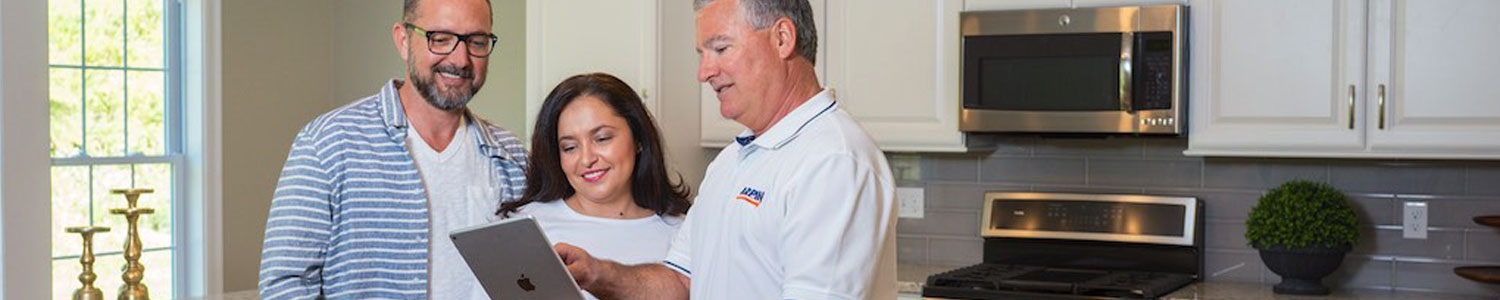couple in kitchen with Arpin rep looking at a tablet