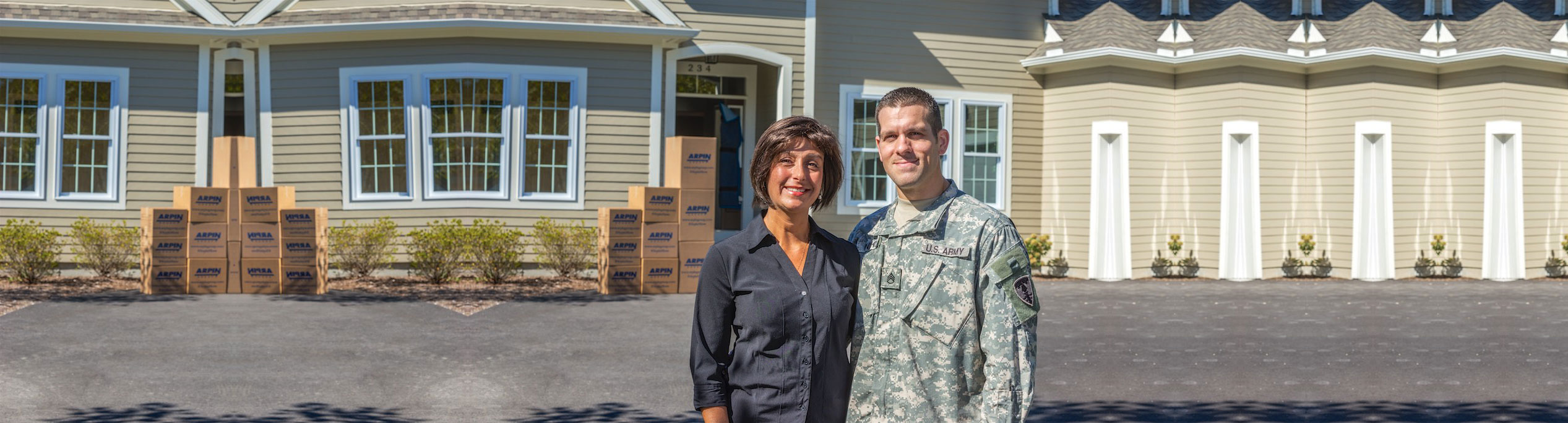 Military couple in front of home