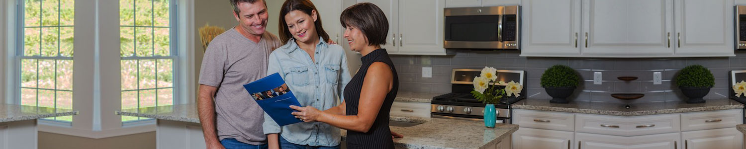 couple with woman in kitchen looking at brochure