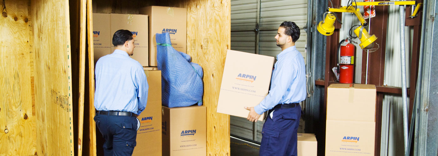 2 men moving boxes in stroage warehouse