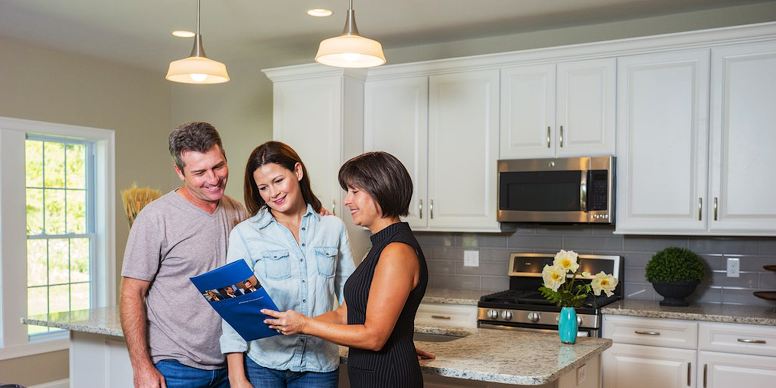 Mover with happy couple in kitchen